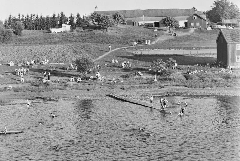 Svart-hvitt fotografi som viser mange mennesker som bader og soler seg. Det er gress på bakken og en lang brygge utover i vannet. I bakgrunnen vises Storhamarlåven.