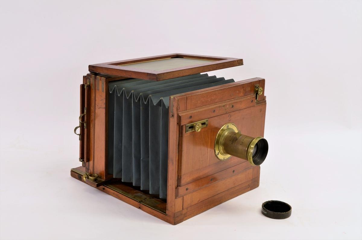 Kamera til produksjon av fotografi på plate, med veske, kassetter, stativ og klede.  A: Kamerahus, Tre (Mahogny?), beslag av lerret, beslag av messing. B: Objektiv. Messing og glass. Med innskrift.  C: Blender av messing.  D: Objektivdeksel av kartong, fløyelskledd invendig. Sort.  E: Stativ, av tre (eik?), tre ben som kan forlenges, messingbeslag.  F: Bag, av seilduk, innvendig kledd med rød fløyel.  G, H, I: Kassetter for to gllassplater i hver, av tre (mahogni?) og messing. Største plateformat 18 x 24 cm.  J, K: Kopieringsrammer, av furu, hjemmelaget. L, M: Pose i svart bomullstoff (nå nærmere fiolett) for oppbevaring av ferdiglagede kasetter.  N: Klede av fløyel (for å gi fotografen mørke).