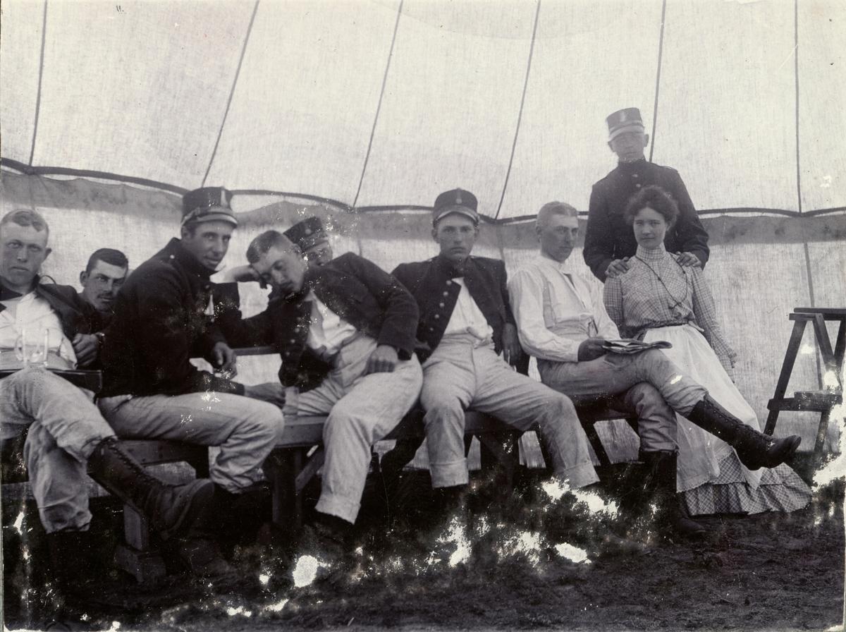 Soldater från Fortifikationen och en kvinna (marketenterska?) sitter på en bänk i ett tält.