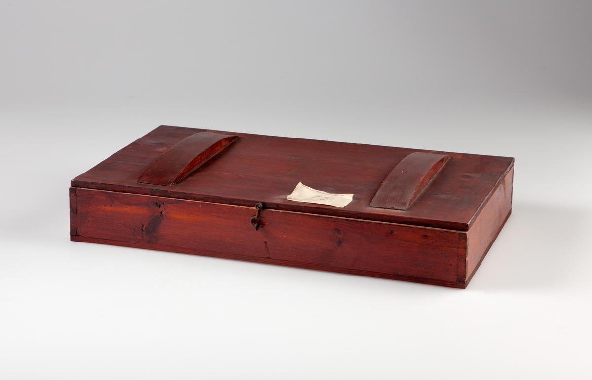 """Kasse av furu, utvendig brunbeiset. Oppdelt i 9 rom på langs og 2 rom på tvers. I hvert rom ligger et areometer. (Ett rom er tomt). På skilleveggen mellom hvert rom er det skrevet et tetthetsintervall som gjelder for det enkelte areometer. Det er to buete trestykker (23 x 4 cm), limt fast på kassens lokk. På lokket av kassen er påklistret en papiretikett med håndskrevet tall """"95"""". Etiketten er delvis skadet."""