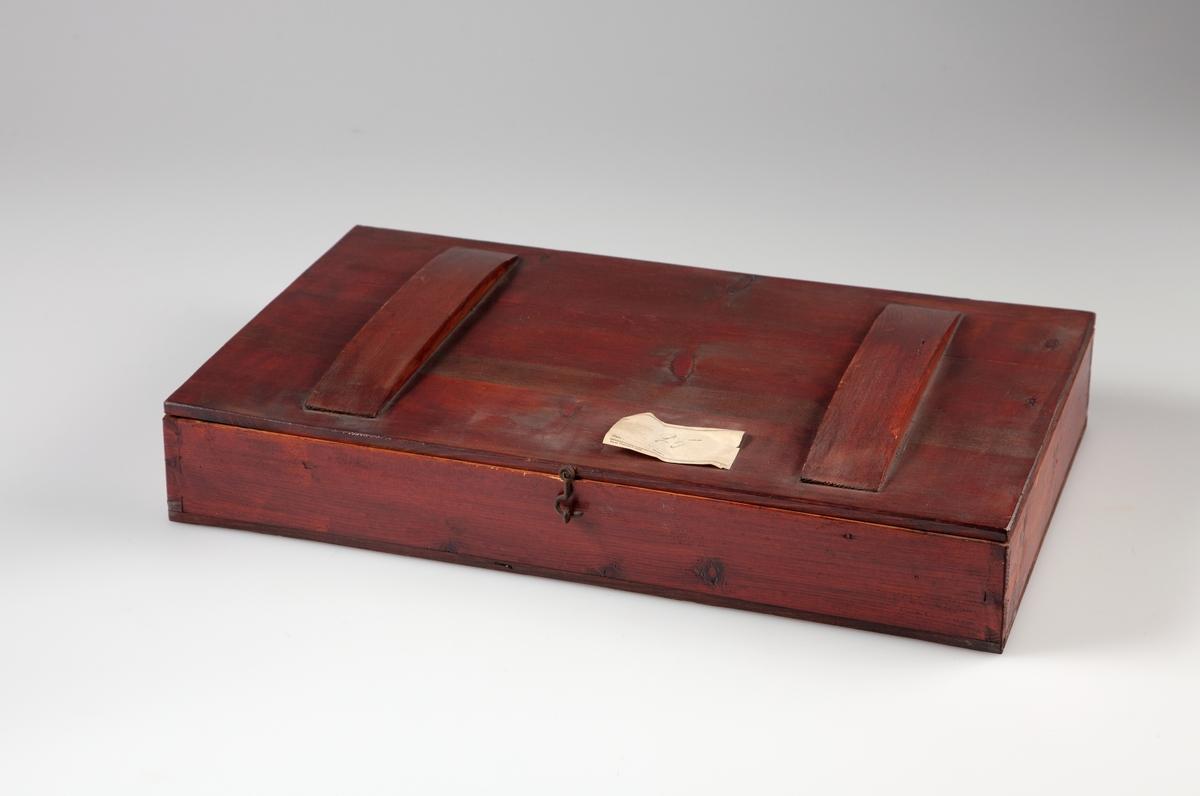 """Kasse av furu, utvendig brunbeiset. Oppdelt i 9 rom på langs og 2 rom på tvers. I hvert rom ligger et areometer. (Ett rom er tomt). På skilleveggen mellom hvert rom er det skrevet et tetthetsintervall som gjelder for det enkelte areometer. Det er to buete trestykker (23 x 4cm), limt fast på kassens lokk. På lokket av kassen er påklistret en papiretikett med håndskrevet tall """"95"""". Etiketten er delvis skadet."""