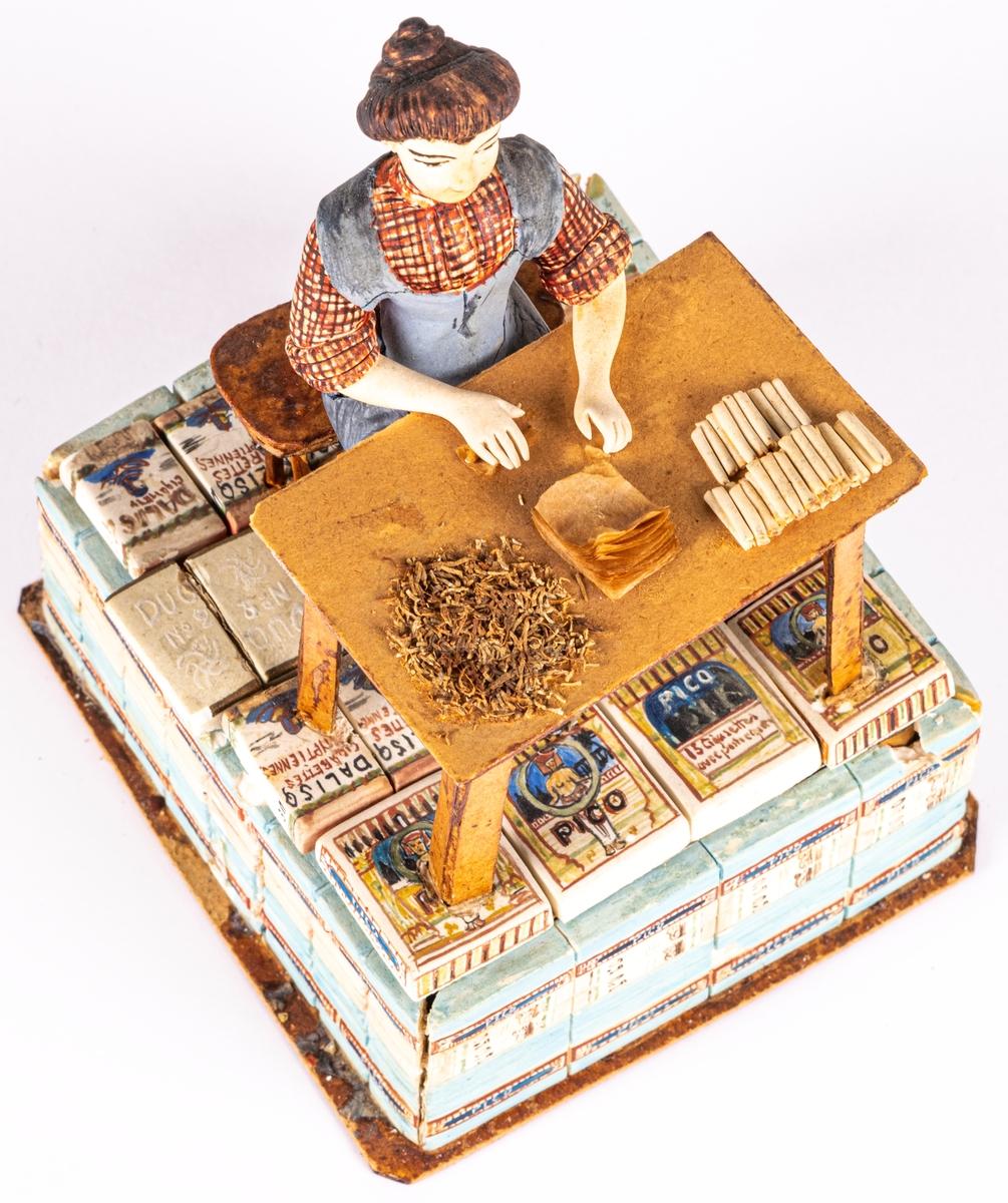 Modell av sockerpasta och papper, dekormålad. Mycket skadat skick. Modellens bas byggd av tändsticksaskar och papp, klädd med små tobakspaket tillverkade av sockerpasta.  Katalog: Modell, visande cigarettillverkning för hand, föreställande kvinna på underlag av små pappaskar.  Lappkort: Modell av gips och trä, målad visande gicarettillverkning för hand av kvinna i grått förkläde, sittande vid ett bord; det hela är placerat på ett underlag av små, hopklistrade oaooaskar, målade såsom oliga cigarettförpackningar.