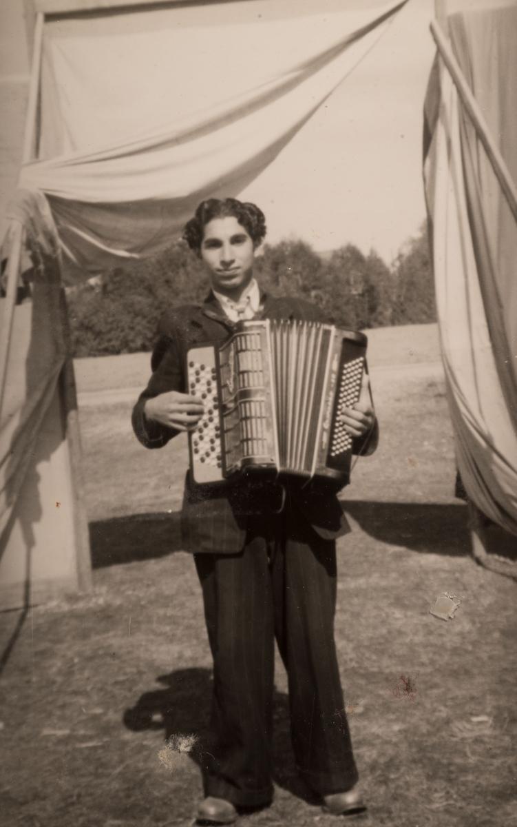 En ung romsk man spelar dragspel. Dukarna i bakgrunden är uppspända för att skärma av lägret och hålla obehöriga utanför. Fotografiet är antagligen taget i trakterna av Sandviken runt 1947