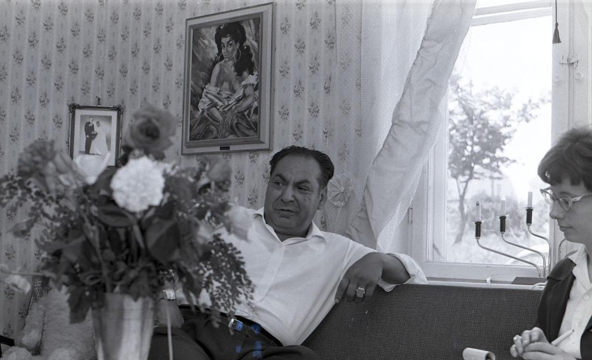 En man sitter i sitt vardagsrum och blir intervjuad av en journalist. Bilden är tagen i samband med ett nyhetsreportage för Skånska Dagbladet. Efter att de svenska romerna i Sverige erkändes som medborgare år 1952 uppstod debatt kring gruppens svåra levnadsförhållanden. En statlig utredning genomfördes under 1954-1956 där en av slutsatserna blev att fast bostad var nyckeln till att lyckas med skolgång och arbetsliv. Från och med mars 1960 hade kommuner möjlighet att rekvirera statsbidrag för kostnader i samband med romers bosättning, vilket förenklade möjligheten för svenska romer att få tillgång till permanenta bostäder samt i förlängningen studier och arbete. Denna process kom dock att bli utdragen under flera år. Frågor om svenska romers förhållanden uppmärksammades mycket i media, långt i på sextiotalet.