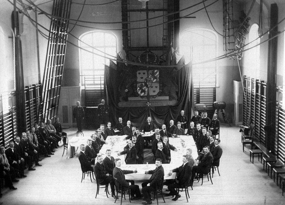 Brandkårsförbundets årsmöte i Stockholm omkring 1900. Ett antal män sitter vid ett dukat bord och längs väggarna i en gymnastiksal.