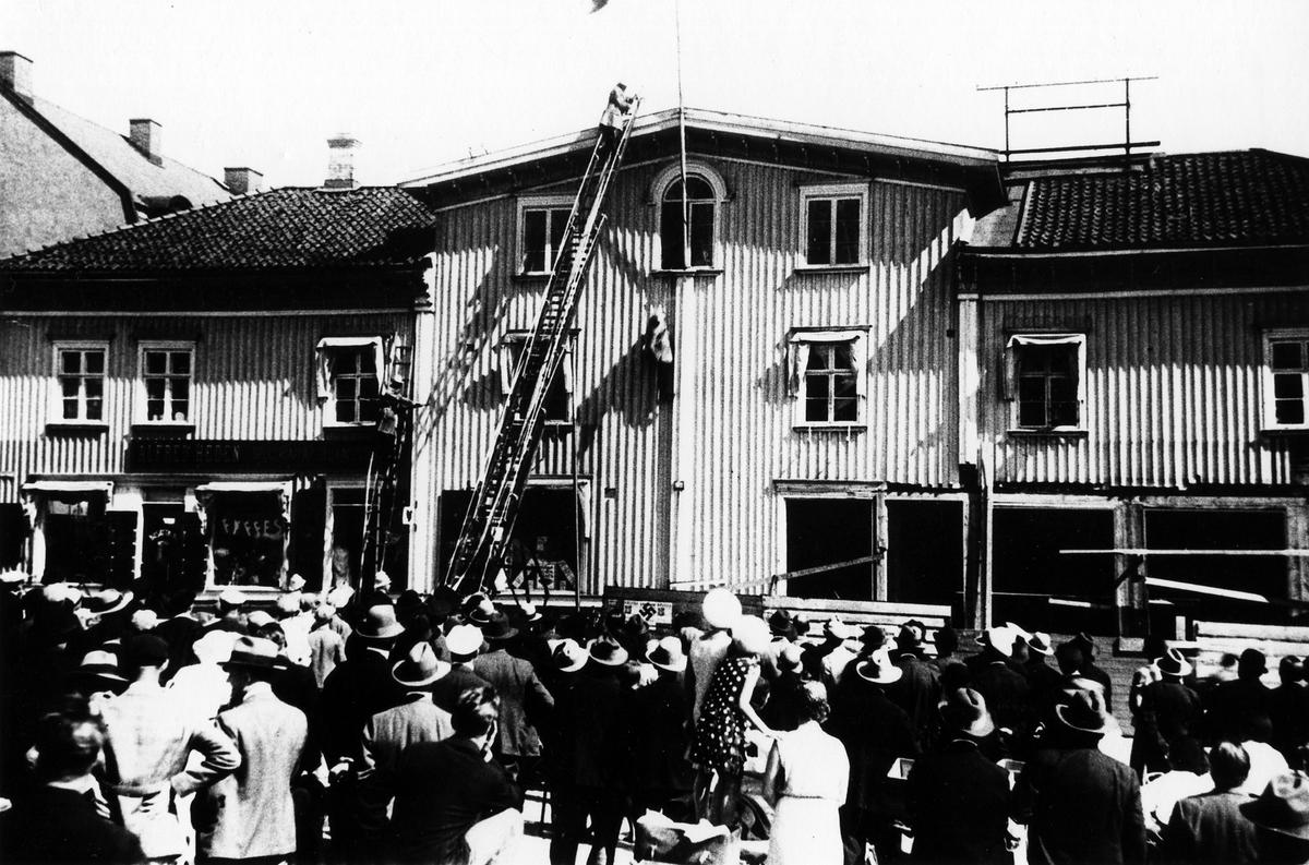 Brandövning i Hedénska fastigheten vid Stora torget, brandmän på stegar inför en folksamling.