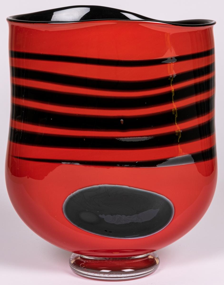 """Vas, blåst, med pålagda färgfält, modell """"Mali"""". Tillplattat oval. Röd med sex svarta tvärränder ovan en svart oval. Rundad nedtill mot smal, ofärgad fot."""