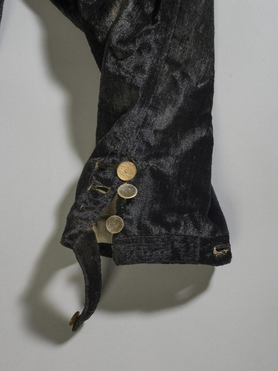 Svart knebukse av plysj med knapper i linning og ved knærne.