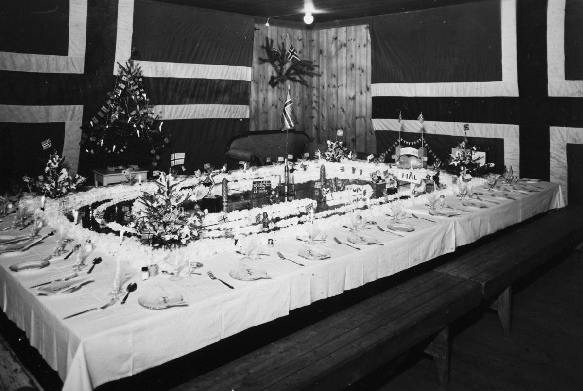 """Fjetre gård, Stange. Bordekking, """"Hamar stadion"""" utført av Anna Sinnerud foran et selskap på Fjetre 20. januar 1945. Diplom til innviterte, se bilde."""