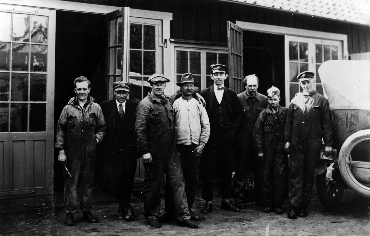 8 män utanför verkstaden i kv Månen 3-4, Alingsås Bil- och Motorverkstad. Längst till höger syns baksidan av en bil. Från vänster: Charlie Hellberg, Katz, Gustav Andersson, Mattson, Eric Johansson, Harald Karlborg, Tore Adestål, Johan Dahlén.