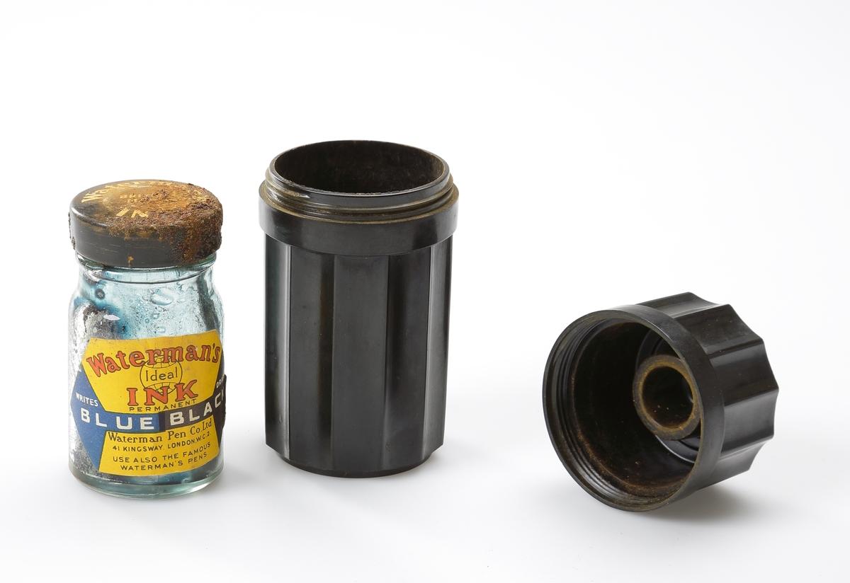 En bläckflaska av glas med tillhörande etui i bakelit. Etuiet har en fjäder i botten som stabiliserar flaskan.