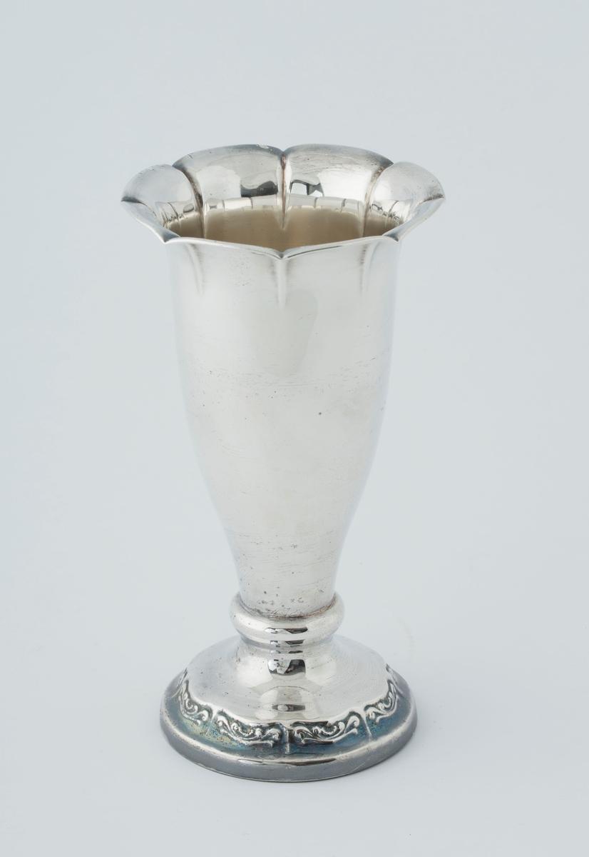 Pokal i sølvplett, traktformet, med vid åpning med mønster. Stett med mønster.