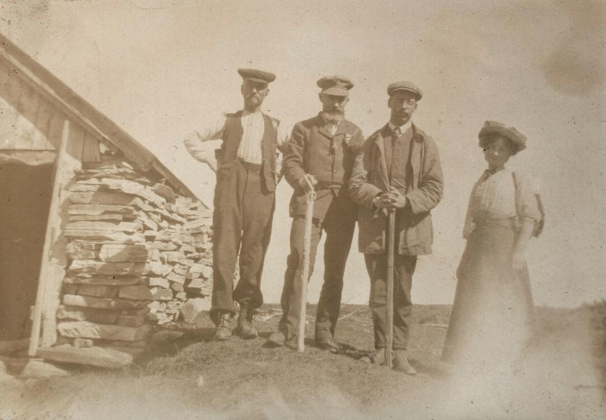 Motiv av tre menn og ei kvinne ved et uthus ved Folkestadvatnet.