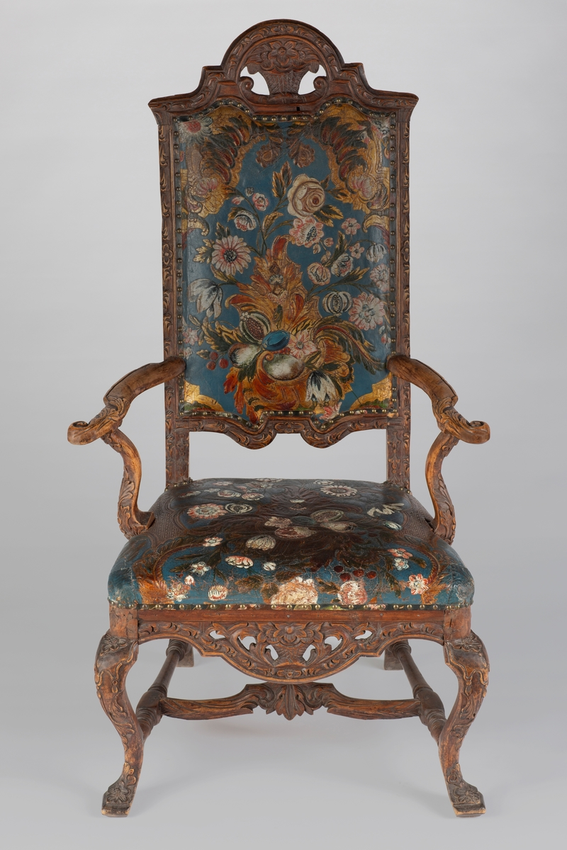 Stolen har utskårne blomsterkurver, blomster og blader. Gyldenlærtrekk med blomster og frukter.