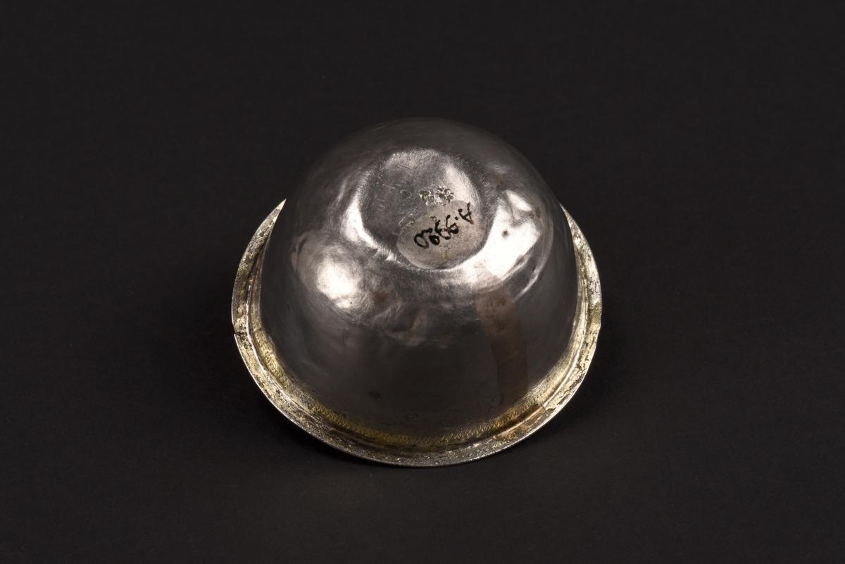 Rund supkopp av silver med liten utvikt kant vid mynningen. Under kanten en inristad sicksacklinje samt förgyllning. Även insidan är förgylld. På sidan initialerna COS. Under är koppen stämplad med Norrköpings stadsstämpel, årsstämpel C (1761) samt HN vilket står för silversmed Henrik Nourin.