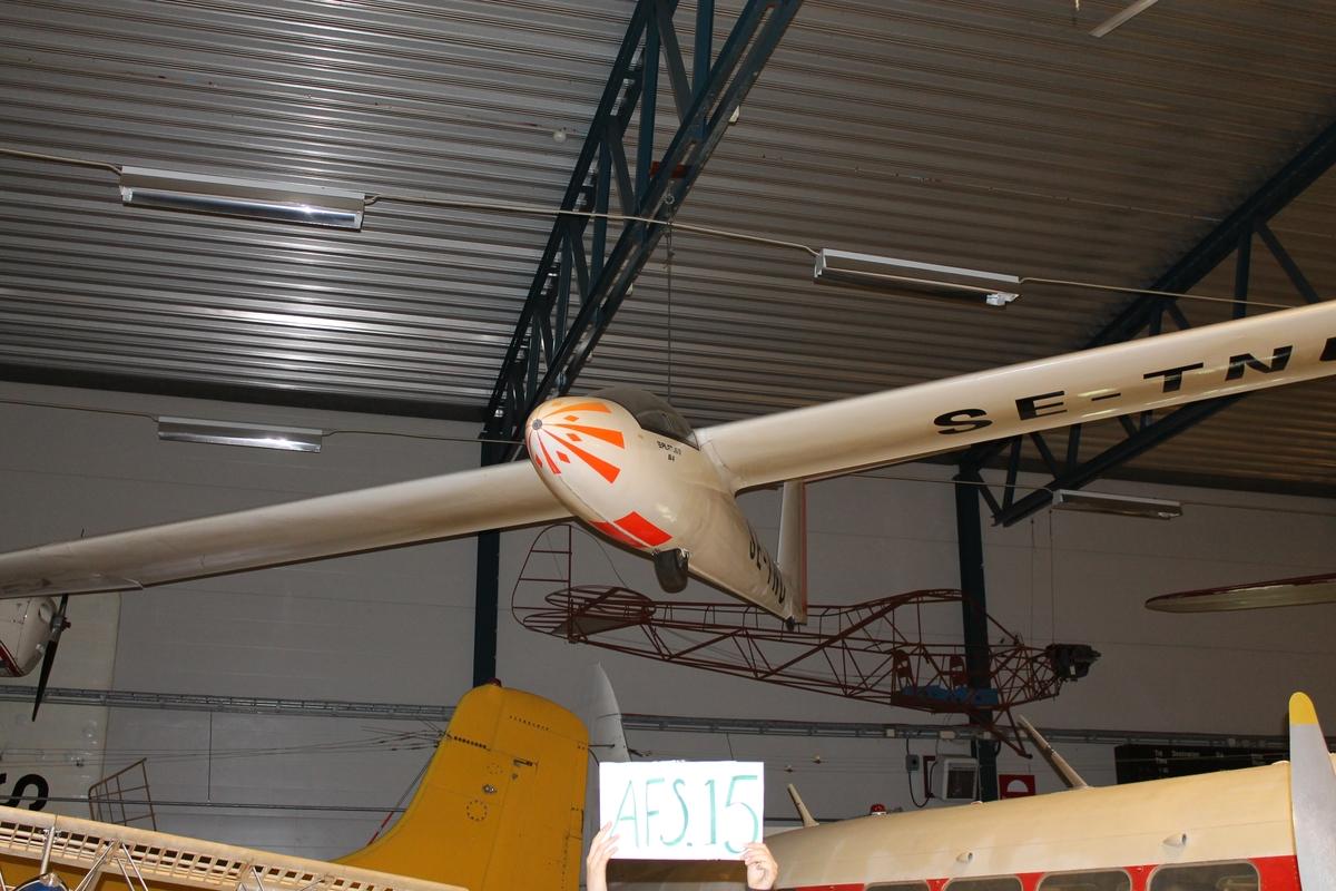 Segelflygplan av modell Pilatus B 4. Ensitsigt plan av plåt med vit flygkropp och vingar samt orange dekor.