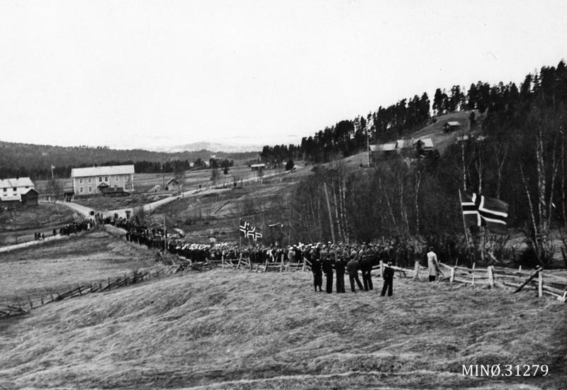 17. mai 1945 i Os. Toget på vei fra skolen og opp mot kirka. Fremst i toget gikk medlemmer av Heimestyrkene. Foto: Musea i Nord-Østerdalen, nr. 31279.
