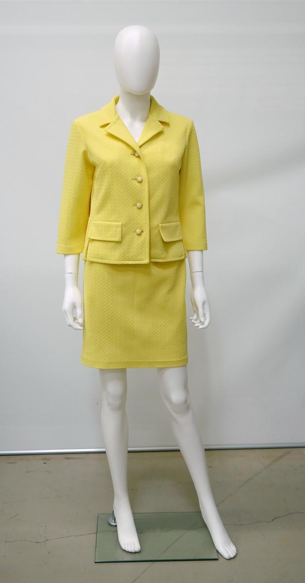 Tvådelad starkt gul dräkt bestående av en jacka och en kjol. Från Martinette AB, Alingsås. Givaren fick dräkten 1967 av sin bror som körde för Martinette. Förmodligen är dräkten ur en provkollektion. Givaren bar dräkten på sin första resa utomlands, till Mallorca 1967. Till den hade hon ett par cerise skor och örhängen.