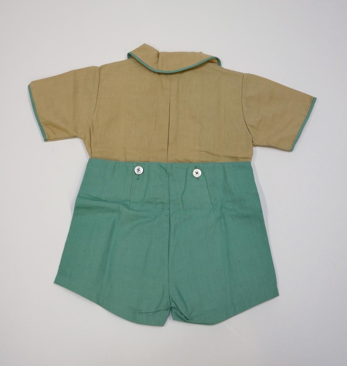 En barndräkt, från 1940-50 tal, bestående av över- och underdel som knäpps ihop i midjan. Överdelen är av skjortmodell med knäppning i halsen och dekorerad med detaljer i turkos samt knappar på bröstet. Underdelen är ett par shorts i turkos. Den oanvända dräkten funnen i Brita Ekwalls hem efter hennes död i december 1993. Brita Ekwall föddes i april 1916 som ett av fyra barn till Alma Augusta Cecilia Gustavsson och Gustav Nikolaus Ekwall, boende på Västgötagatan i Alingsås. Brita Ekwall gifte sig aldrig och levde kvar i sitt barndomshem hela livet.