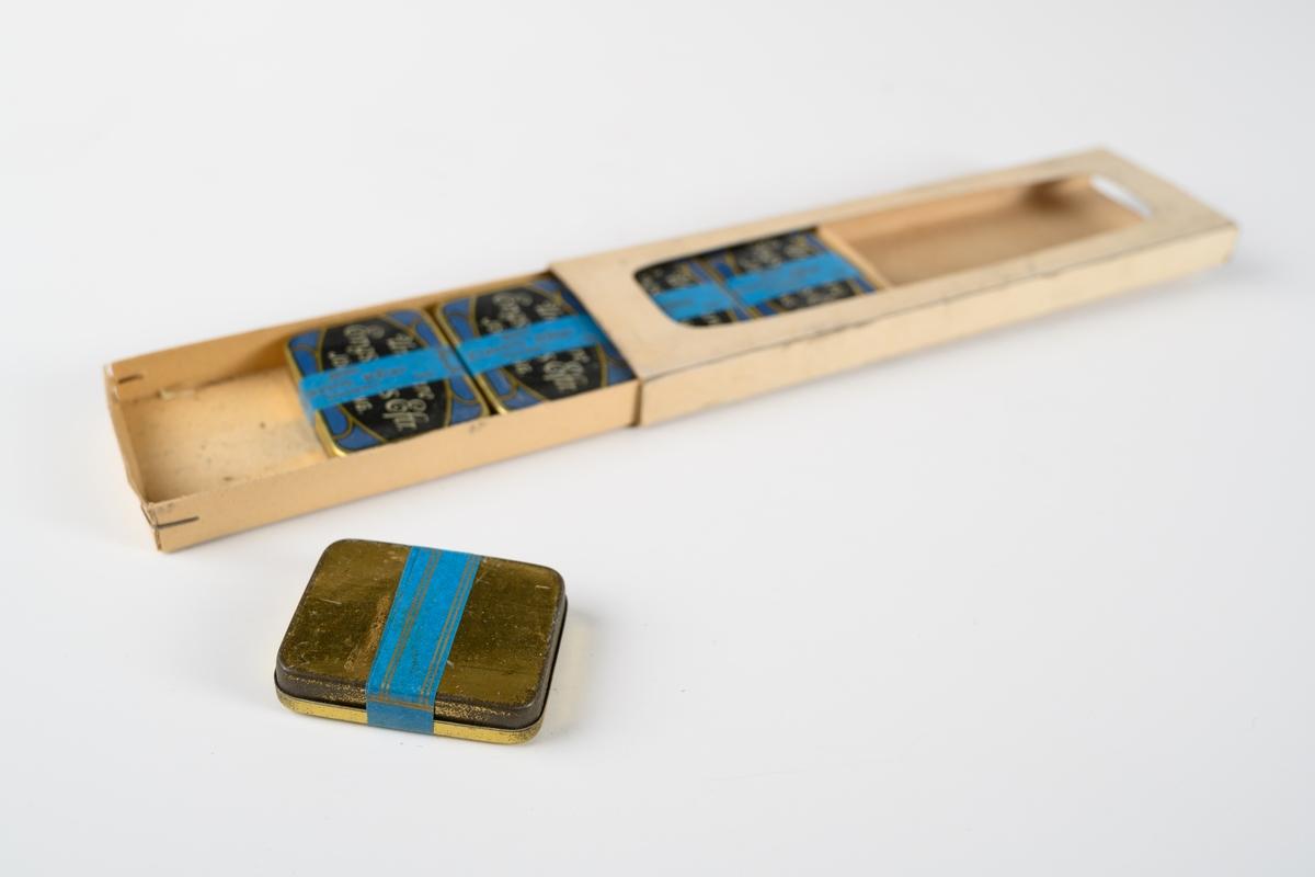 """Förpackning av papper innehållande fem mässingslaskar med grammofonstift för spelning av stenkakor. Varje ask innehåller 200 nålar. Askens lock har tryckt dekor i blått och guld, och svart etikett med guldtext: """"Urmakare Engströms Eftr. JÖNKÖPING."""". På en blå pappersbanderoll runt varje ask är tryckt: """"200 Electric Nålar Consert Imp.""""."""