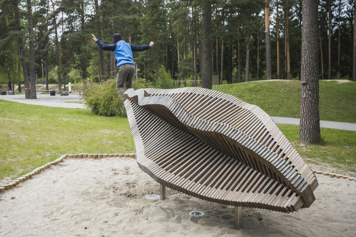 Skulptur utformet i tre. Skulpturen utgjør en flytende form bestående av trespiler. Plassert i skolens utemiljø blant grantrær foran nytt administrasjonsbygg.