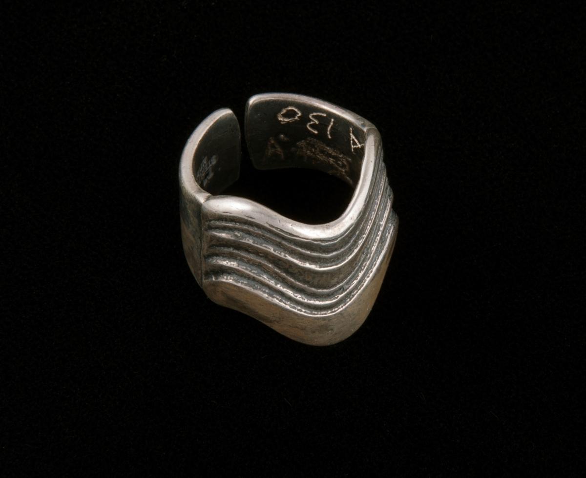 Støpt, blankpolert ring av bredt sølvbånd med regulerbar åpning på undersiden og dekorert parti på oversiden. Dekor av 5 parallelle nedhengende og stiliserte bølger i ringens lengderetning. sidekantene buer på samme måte.