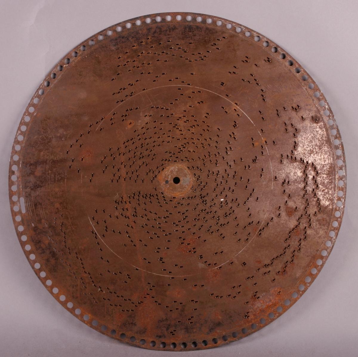 """Perfortert metallplate med pigger på undersiden. Programmert musikk for platespilledåse. 76-spor, Ø 40 cm. Drivsystem: perifere hull langs kant (ø=7 mm) for perifer tannhjulsdrift, samt et 19 mm avlangt hullfor å markere slutt/stopp.  Sentrumhull, diameter: 8 mm, samt et """"satelitt-hull"""" ved siden (ø=4 mm) på RMT 932 M-Ø, AB,  AD-AF, AH-AM, AP-AT (31 stykk). U-formet pigger på underside av platene.  NB! riller for hvert spor på underside!"""