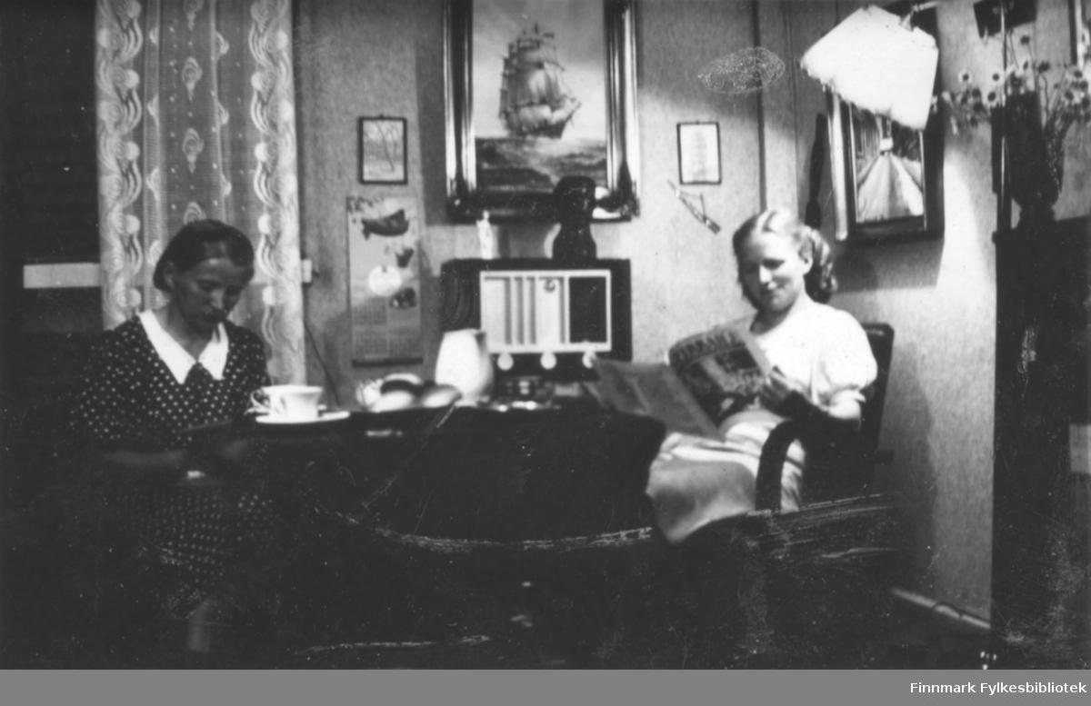 To damer sitter i stua og leser. Kaffekopper, boller i en fat og en kanne er på bordet. Radio i bakgrunn, noen tavler i veggen. Bildet er muligens fra Salttjern?