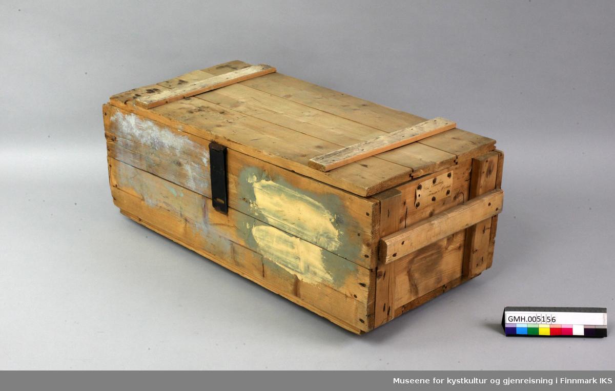 """Denne grove kassen er spikret sammen av bord som er sammenføyd med not og fjær. Lokk og bunn består av tre, sidene av to bord. Foran har den et låsbeslag som mangler den delen som hengelåsen settes i. Kassen har to solide håndtak av lekter på sidene. På en av sidene er det stiftet fast et pappetikett med påskriftet """"Karl Planting Tromsö -H-fest""""."""