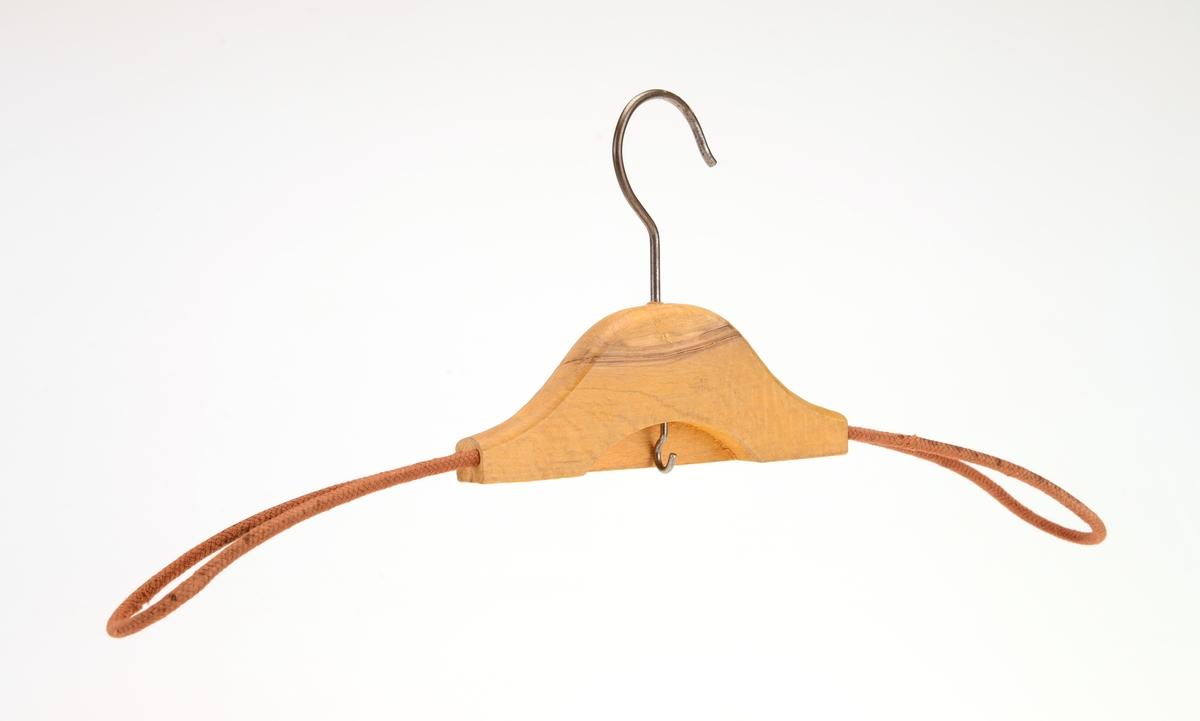 En kleshenger laget av tre, metall og tekstil. Midtpartiet er av ubehandlet tre. På hver side går det ut en arm laget av stofftrukket metallbøyle (bøylen er dobbel). På den ene siden på midtpartiet er det skåret ut en bue. I denne buen er det skrudd i en metallskrue. For oppheng er det en enkel krok i metall.
