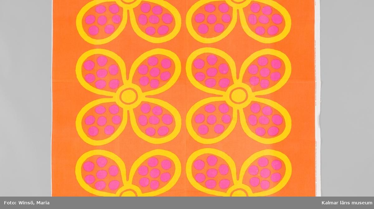 KLM 46157:691. Tyg. Metervara. Tryckt mönster på vit tuskaftad bomull.  Mönster med stora parställda gula blommor, rosa prickar på blommornas kronblad, mot orange botten. Tryckt orange text i höger stadkant: MONA DESIGN HANS KRONDAHL SÖDRA KALMAR LÄNS HEMSLÖJDSFÖRENING KALMAR. Kortsidorna fållade för hand med tråckelstygn.