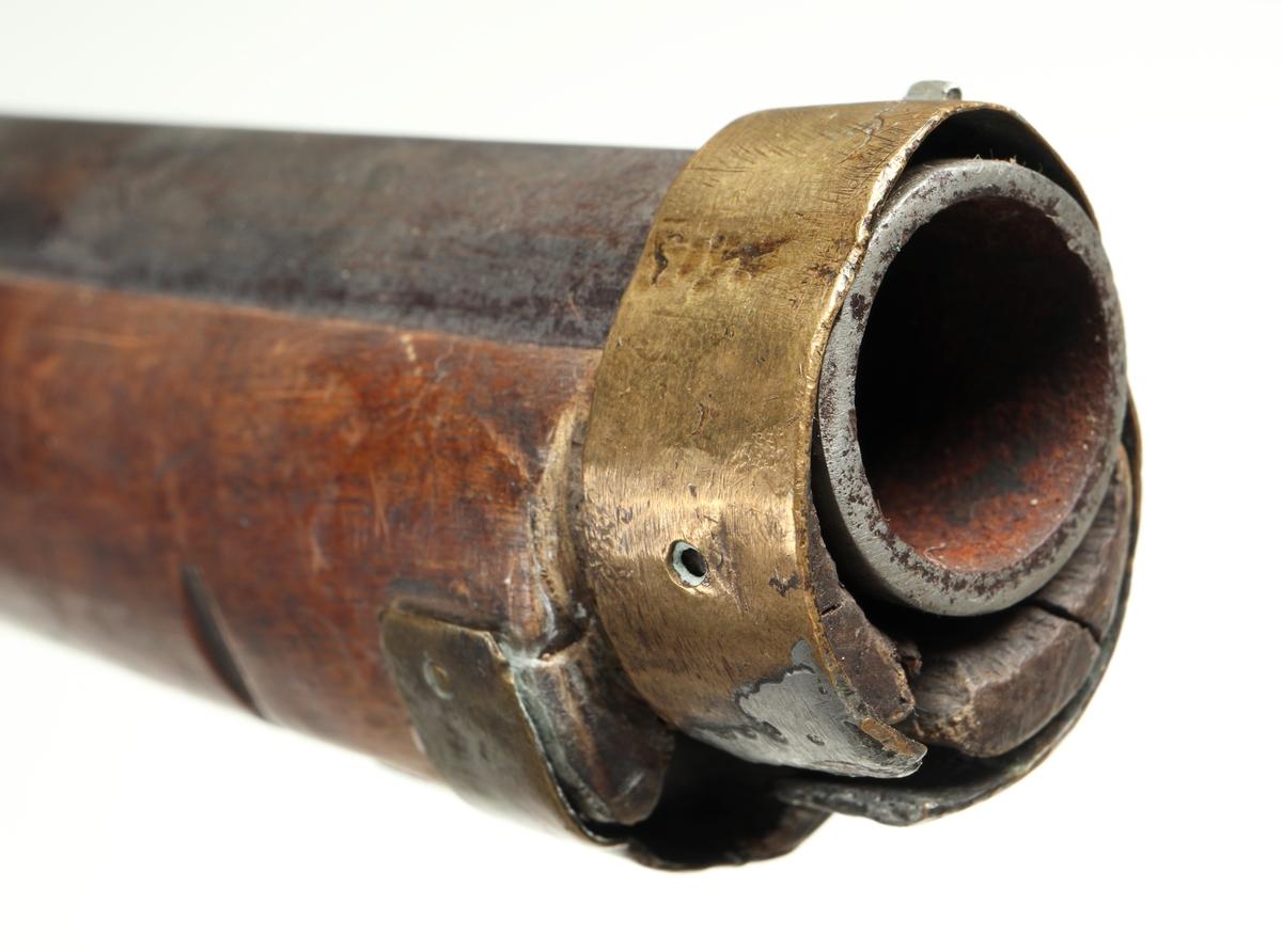 Slaglåspistol omändrad från flintlås. Framstocken har en laddstocksränna under pipan. Kolvkappa, sidobleck, varbygel och näsband är tillverkade av mässing. Pipan är rund och försedd med ett ståndsikte placerat bak vid svansskruven, samt ett mässingskorn framtill på näsbandet. Pipan är slätborrad och har en innerdiameter på ca. 18mm.  Pipan och främre delen av framstocken är avkortade. Ursprungligen har vapnet varit i ett längre utförande. Vapnet är troligen militärt ursprungligen, men omändrat och avkortat av lokal smed eller liknande. Inskrivet i huvudkatalog 1927.