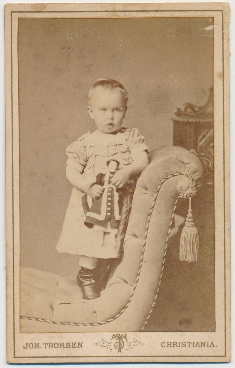 Lita jente stående i stol med dukke, ukjent