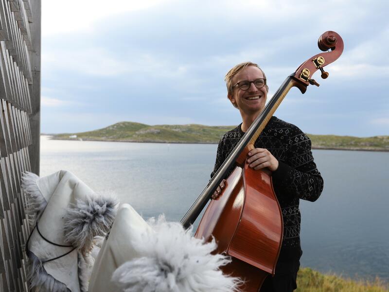 Sigurd Hole poserer med sin kontrabass utenfor en trehus ved vannet, lave fjell i bakgrunnen.