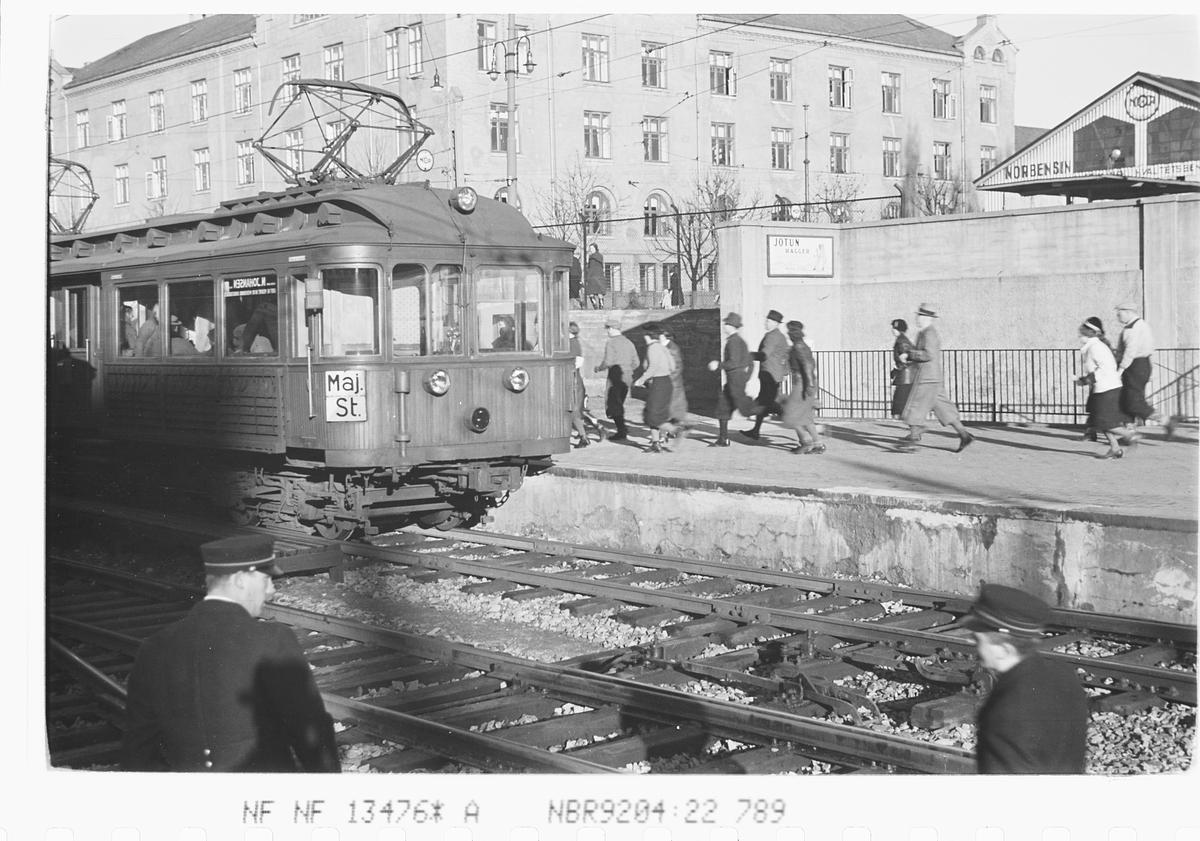 Personer løper til T-banen ved Majorstuen stasjon, Oslo. Fotografert 1940.