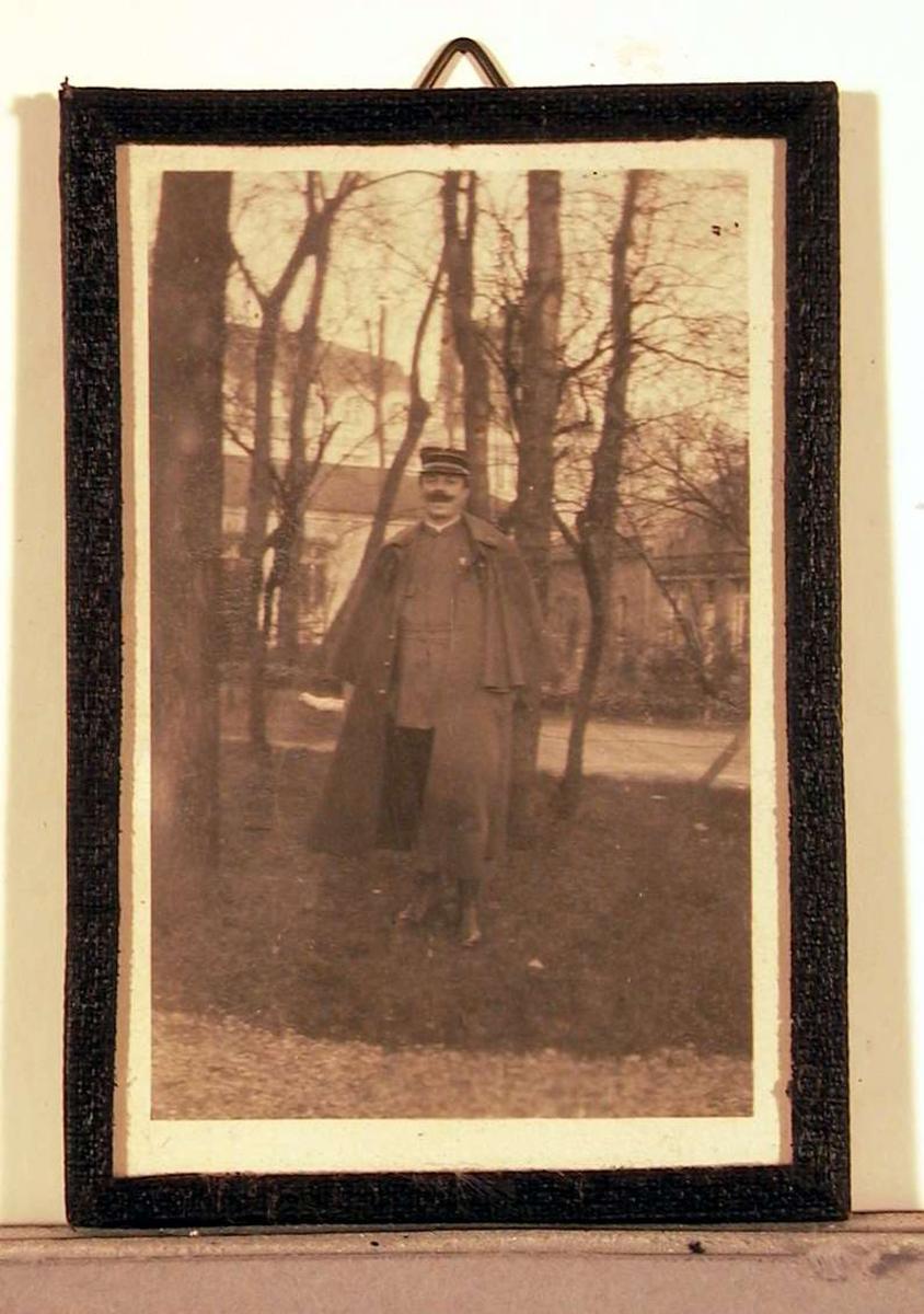 Fotografi; utendørsopptak: en voksen mann i militæruniform med stor lang kappe over skuldrene. I bakgrunnen skimtes en stor bygning og en del trær.