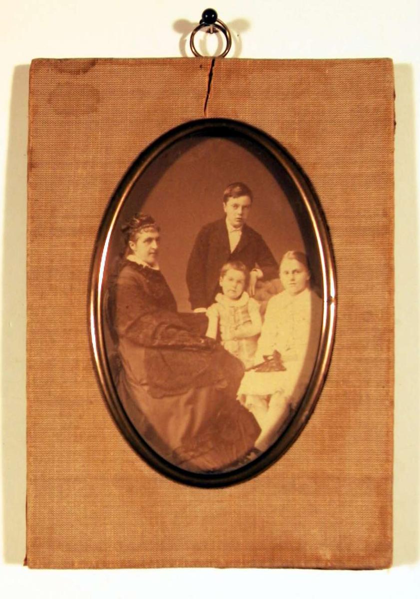 Fotografi av mor med tre barn, en gutt i mørk dress stående bakerst, en liten pike stående i midten mellom mor sittende på stol i mørk lang kjole og stor pike sittende til høyre i hvit kjole med mammelukker.