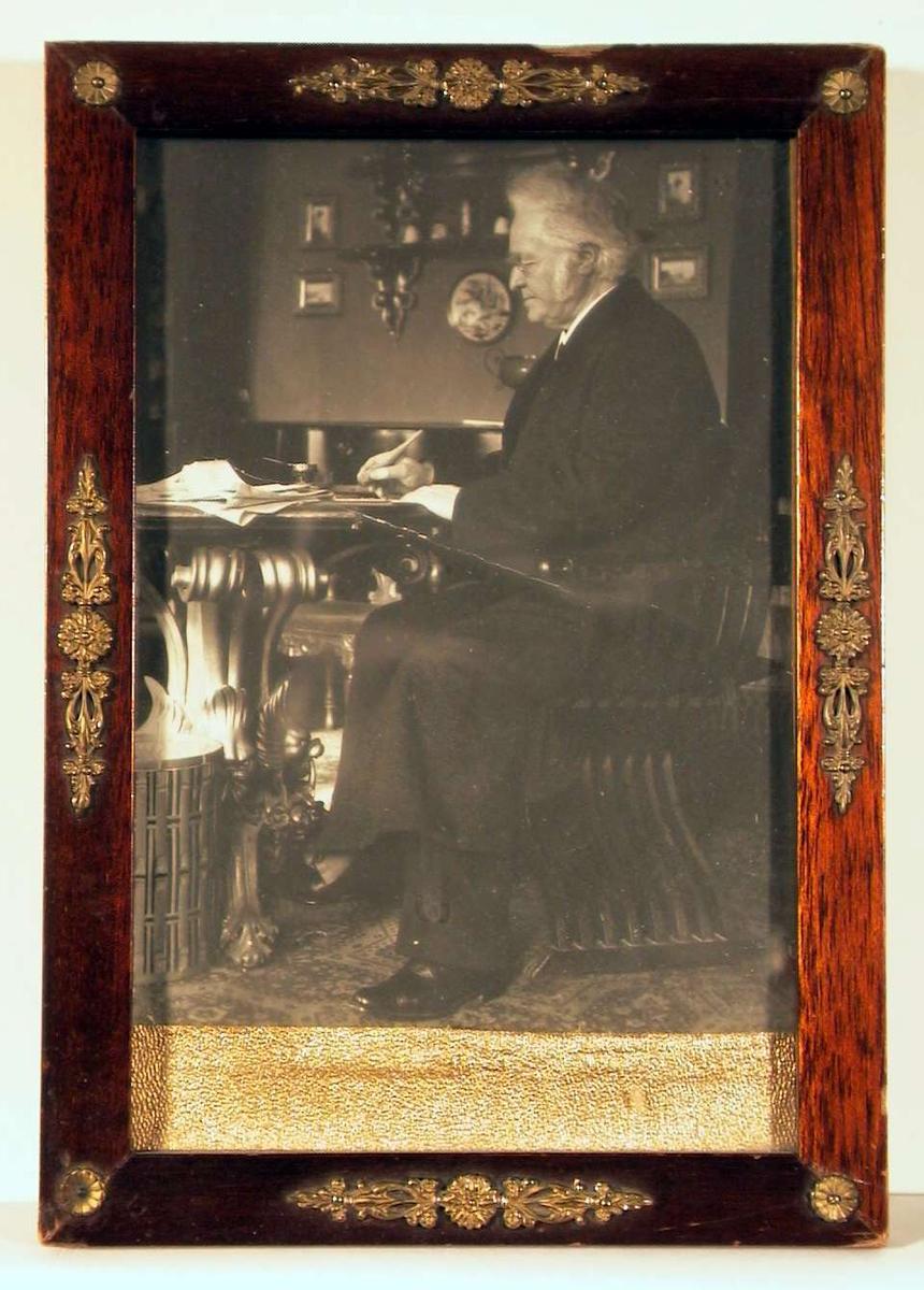 Fotografi av dikteren sittende med korkpenneskaft i hånden på en egyptisk inspirert stol ved stuebord fylt opp med papirer.