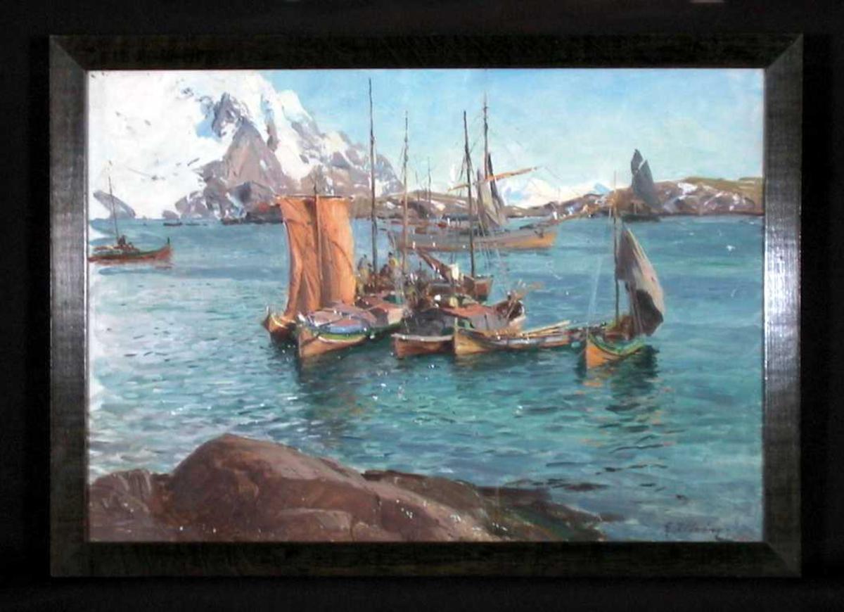 Sjø med svaberg i forgrunn, en klynge fiskebåter og Lofotveggen med snø i bakgrunn.