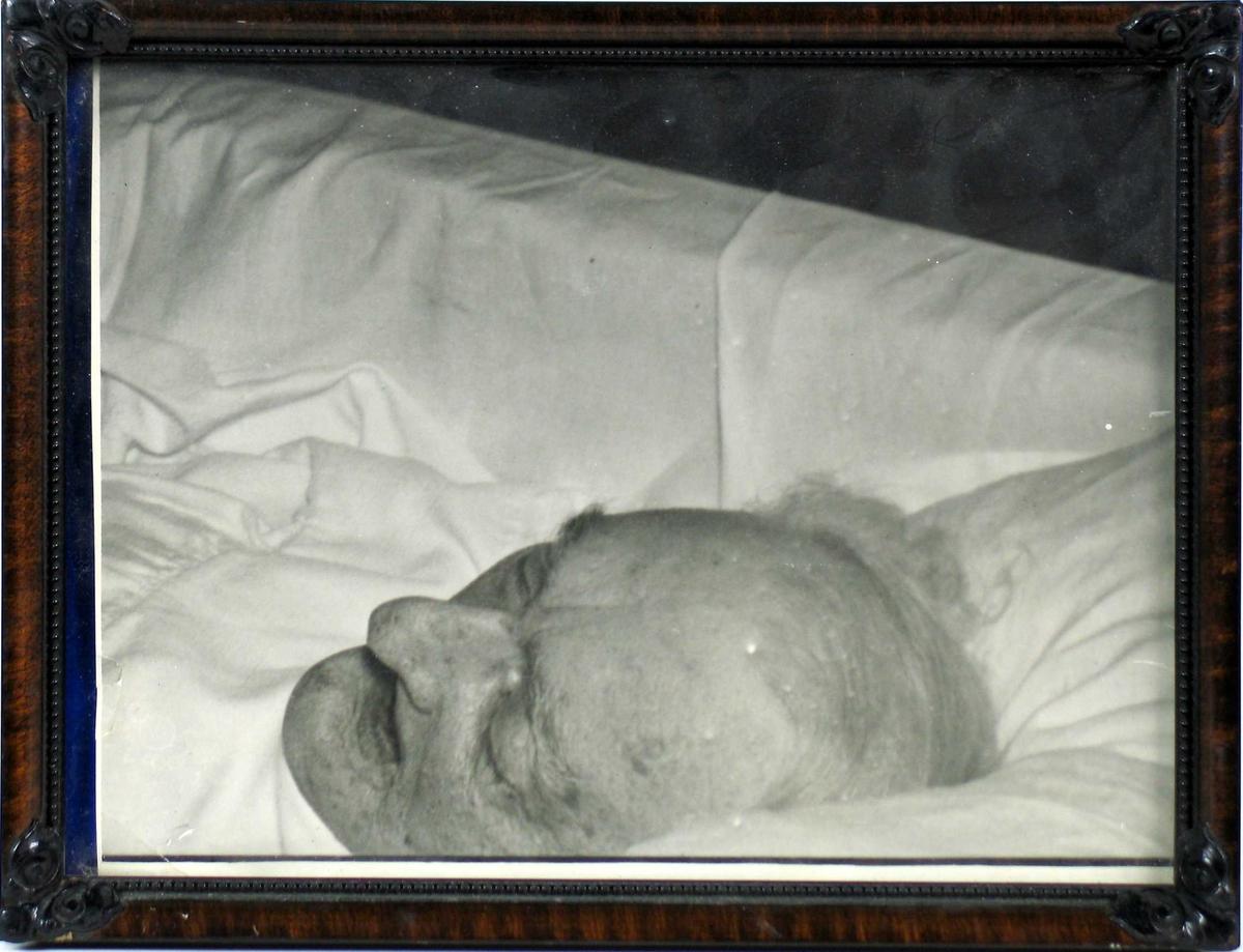 Død kvinne i hvit kjortel liggende i kiste.