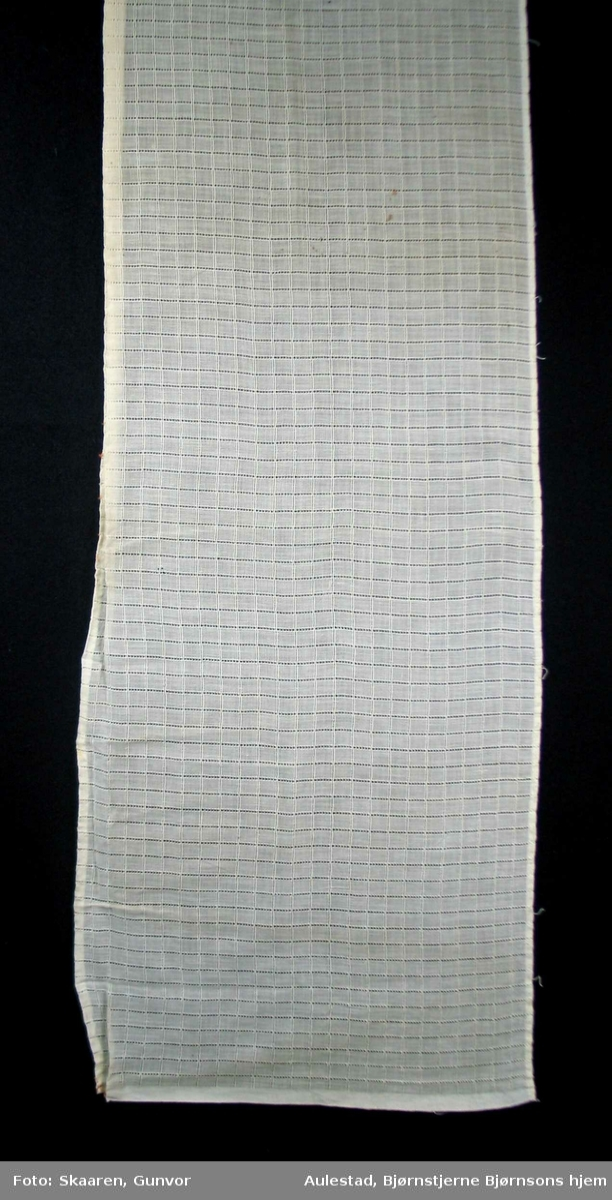 Hvit undergardin i gjennombrutt bomullsstoff. Striper både på langs og tvers danner ruter, ca.1cm.
