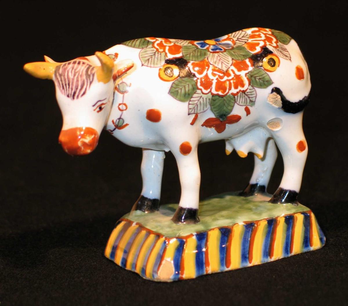 Ku laget i fajanse med flerfarget fantasimønster. Står på et lite blått og gulstripet fotstykke.