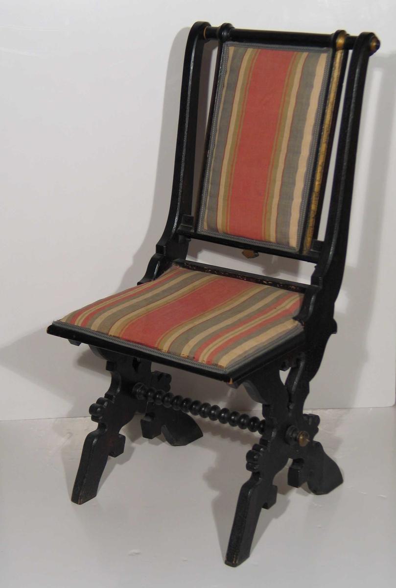 Svartmalt stol med kraftige profilerte bukkeben og kuledreid sprosse mellom. Rygg og sete trukket i et flerfarget stripet stoff. Gullmalte detaljer på rygg og sprosse.