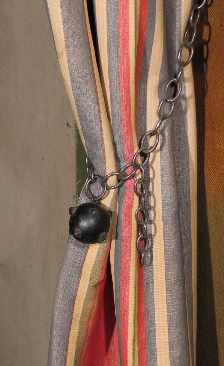 Portiere med kappe i stripete bomullsstoff i fargene rødt, gult, grått, hvitt, gulgrønt og brunt. Striper i ulike bredder, rapport 32,4. Sideportiere og kappe fôret med gul bomullssateng. Isydd små ringer med liten fold for hver som danner rynkehode. Mercerisert renning. Portieren er holdt til siden med en svart kjetting med trekule dekorert med pyramideformede nagler.