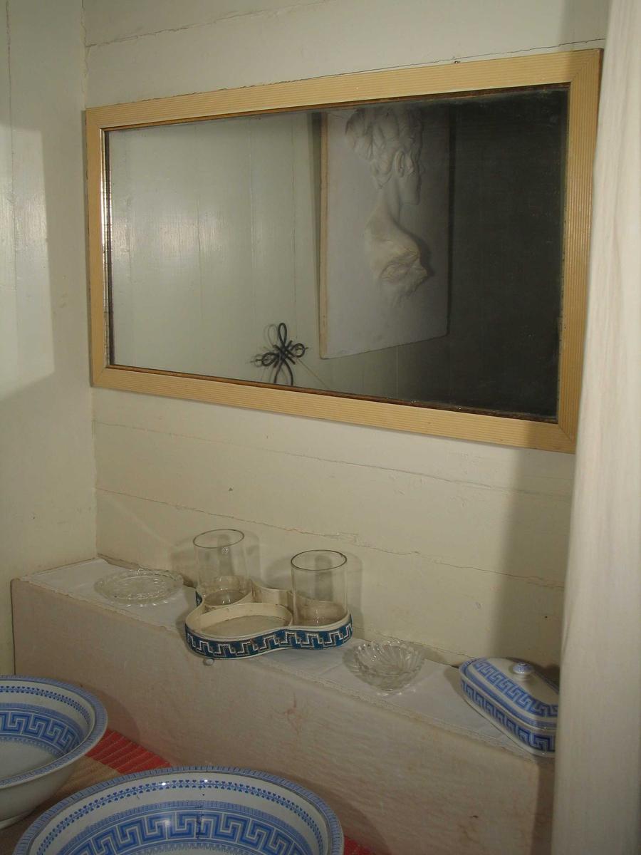Rektangulært speil med riflet hvitmalt ramme i tre. Den har en gyllen kant innerst.