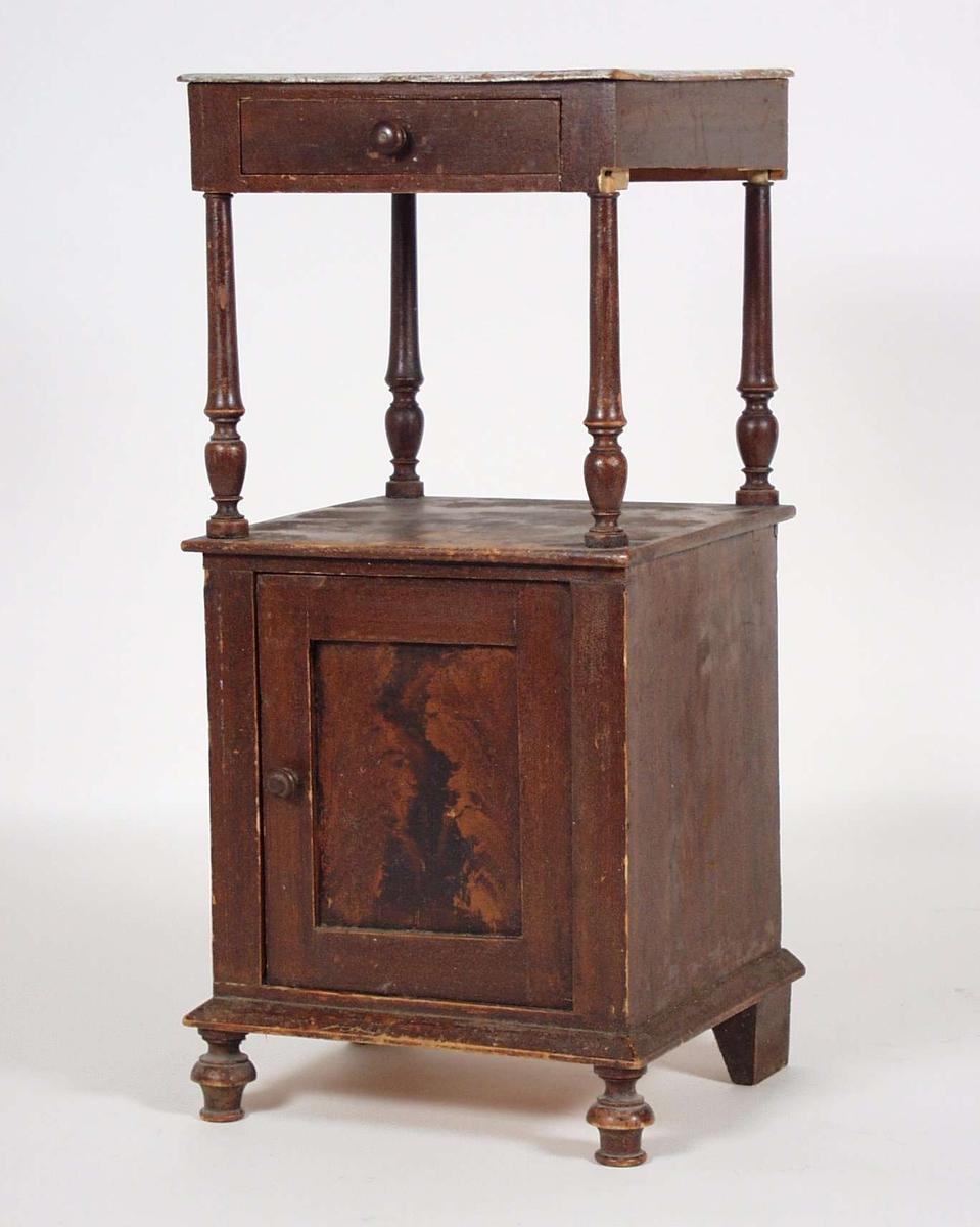 Nattbordet er av gran og muligens av et treslag til. Det er ådret og bordplaten er malt hvit. Fire dreide hjørnestolper bærer den øverste skuffen med bordplaten. Disse stolpene har løsnet.