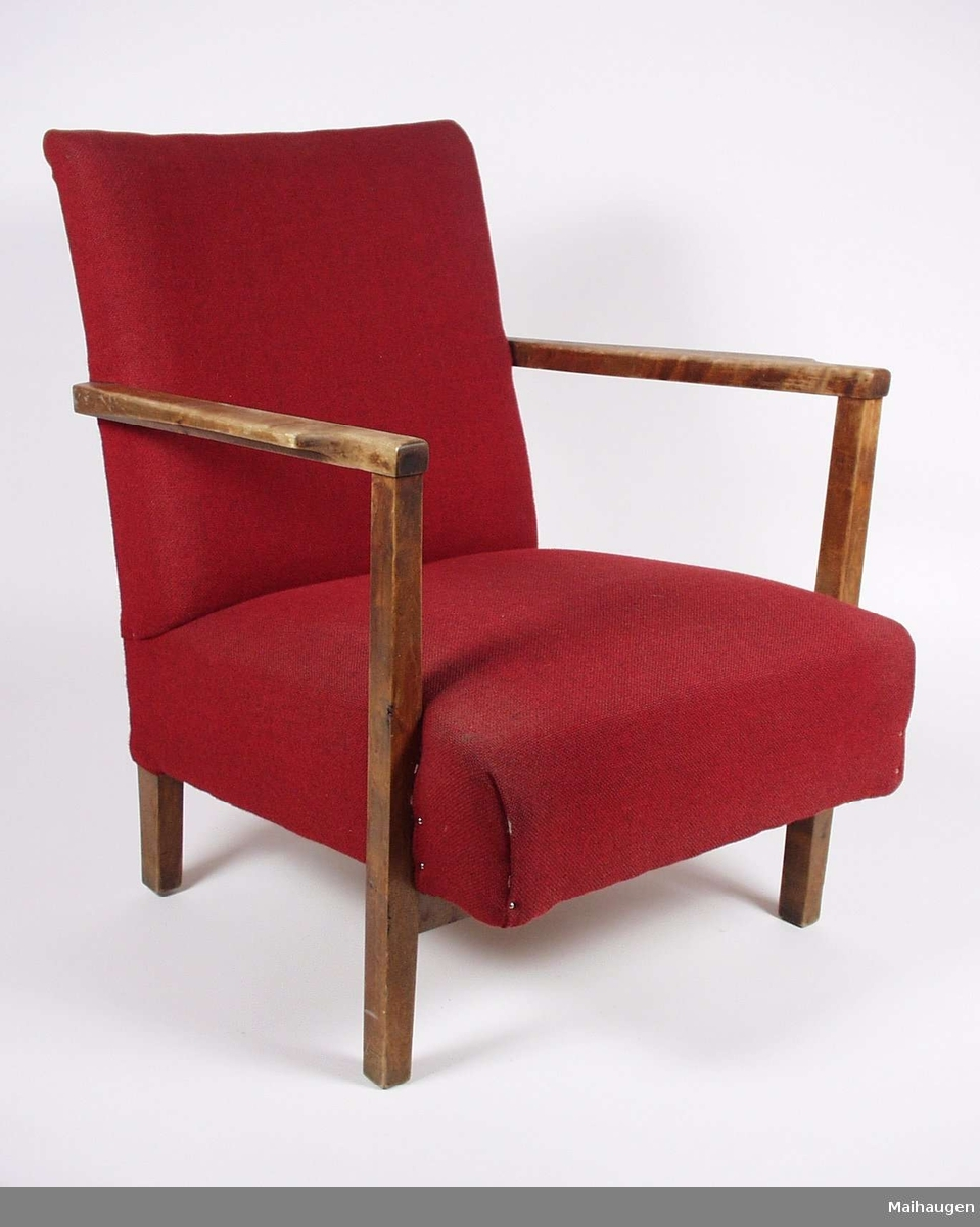 Stolen er i bjørk og gran, med stoppet sete og rygg i rødt ullstoff.