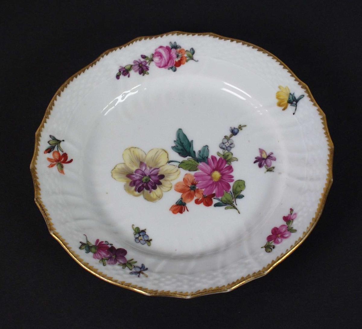 Hvit asjett i porselen med håndmalt blomsterdekor og gullkant. Den er riflet i godset.