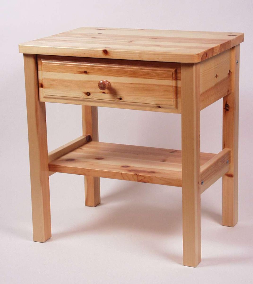 Nattbord i lakkert furu med skuff og hylle nederst. Bordplaten har avrunda hjørner og fronten har utfreste detaljer.