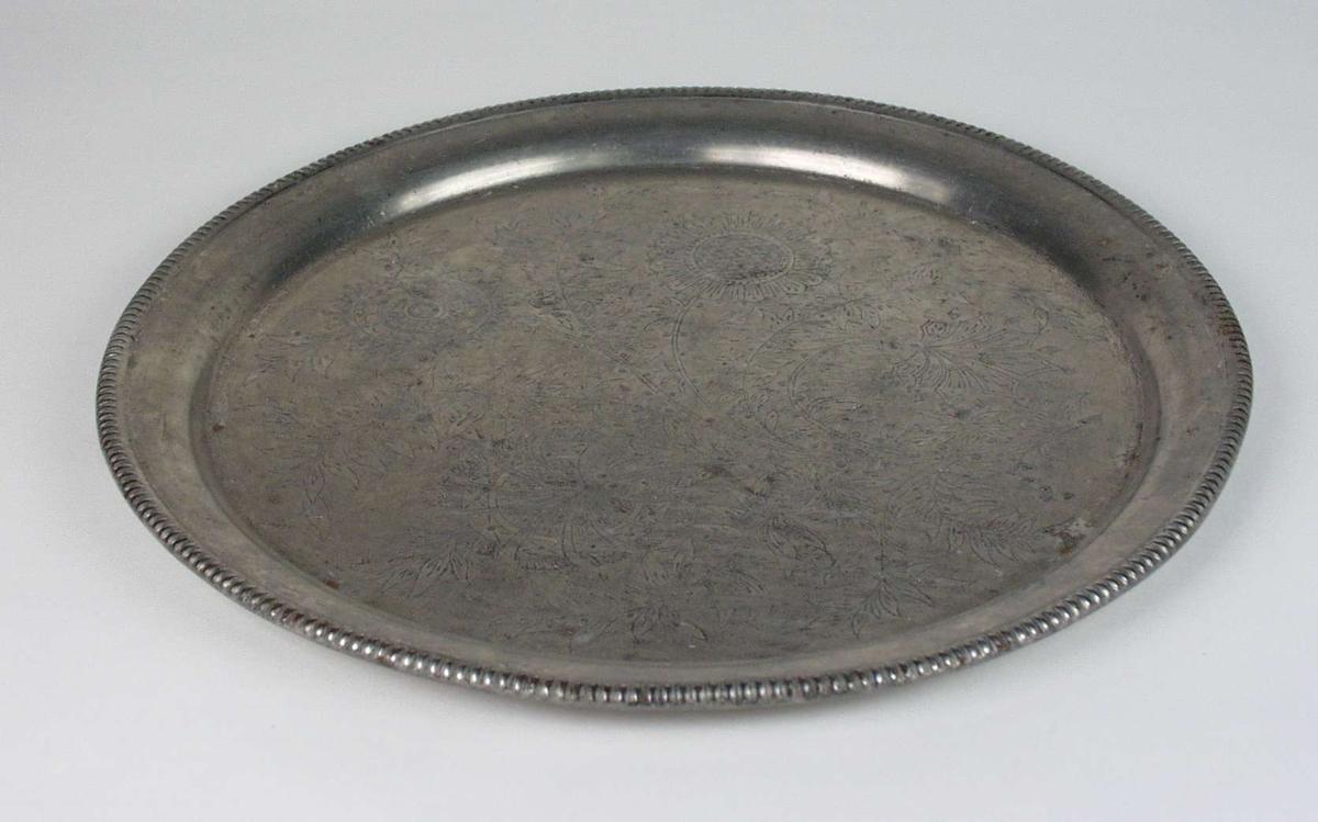 Rundt serveringsfat i metall med trykt blomsterdekor.